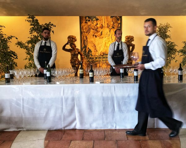 A waiter walking by and two people pouring at En Primeur 2018