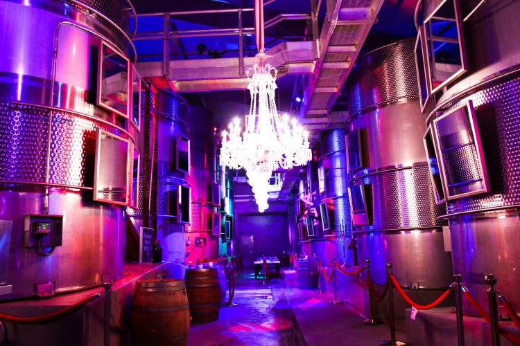 The Crystal Room with a huge glowing Chandelier next to Fermentation tanks and an exquisitely elegant tasting room at Raymond Vineyards