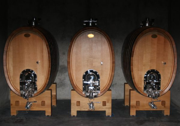 In the cellar of Promontory with three large wooden barrels holding the latest vintage