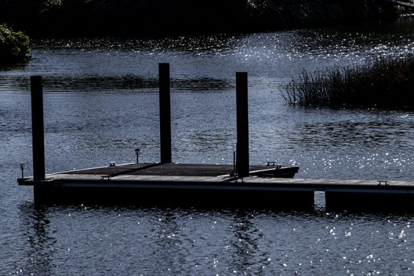 sparkling Napa river with Boat dock and greenery in the summer sun